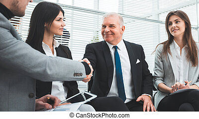 business partners shaking hands after discussing a new contract.