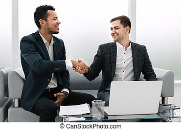 business partners shaking hands after discussing the contract.