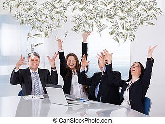 Portrait Of Businesspeople Throwing Currency Note In Office