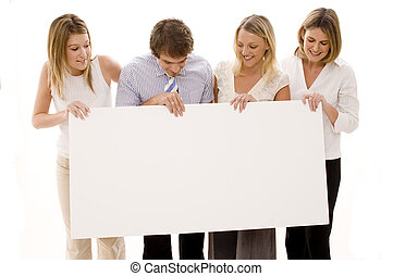 Four young executives holding a big blank sign
