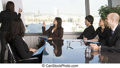 Businesspeople are discussing the work, or a salesperson or investment adviser is talking very friendly to clients, good customer relationship, group of persons is wearing business clothes and sitting at a table, interview or consultation at the bank, banking activities,