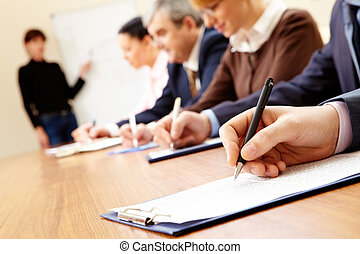 Close-up of business people writing text during business training