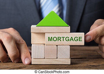 Businessman Building House With Mortgage Block