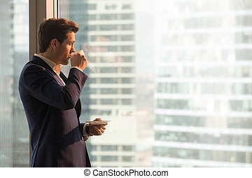 Businessman enjoying morning coffee in office