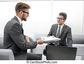 businessman giving a colleague the financial documents
