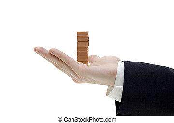 businessman holding a pile of bricks