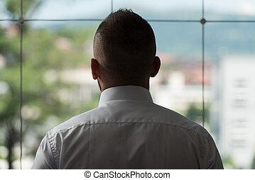 Businessman Looking Through Office Window