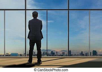 Businessman looking through window