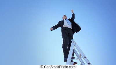 A businessman in a suit and tie and standing on a ladder raises a proud winner fist up against a clear blue sky.