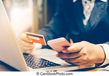 Businessman using credit card and smartphone with a laptop to purchase online