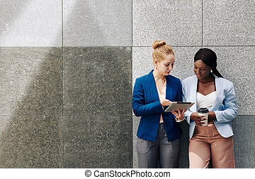 Businesswoman showing article to colleague