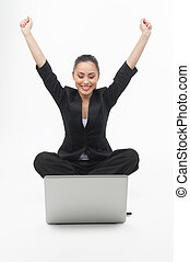 Businesswoman with laptop. Cheerful young businesswoman looking at the computer monitor and holding her arms raised while isolated on white