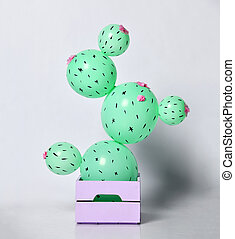 Cactus balloon in pastel purple flower pot made of green round balloons with flowers. Creative idea