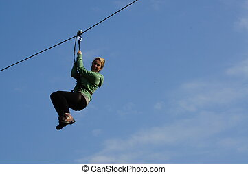 Girl on a zip wire in a tree canopy