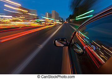 Cars driving through the city with such speed that the lights of the city reserves the long tracks