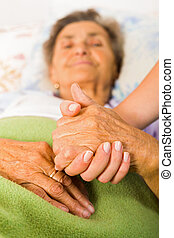 Care help love and trust to elderly people - holding hands.