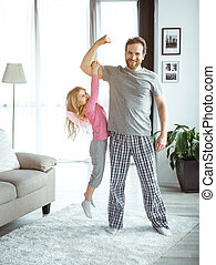 Carefree father and daughter playing at home