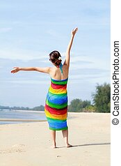 Carefree woman dancing on the beach.