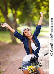 carefree young woman arms open outdoors