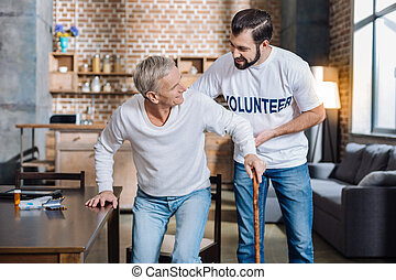 Careful attentive volunteer helping a senior man to stand up