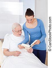 Caretaker And Senior Man Reading Book
