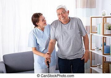 Caretaker Assisting Senior Man While Walking At Home