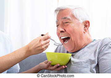 Caretaker Feeding Senior Man