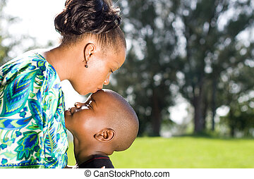 a caring african mother kissing her sons head
