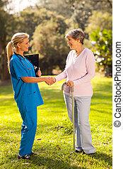 female nurse greeting recovering senior patient