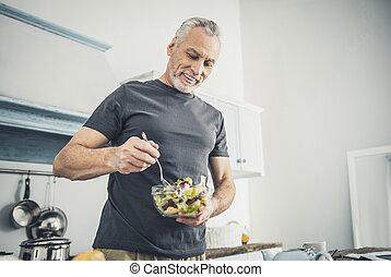 Caring husband cooking salad for dinner
