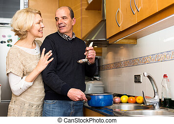 Caring senior husband cooking meal