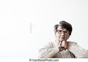 Catholic elderly woman praying to god with copy space