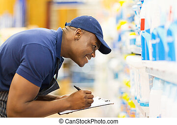 african hardware store worker taking stock