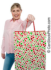 Cheerful blonde girl holding shopping bag in outstretched arm