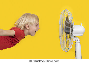Cheerful boy with blond hair flies to the fan. Summer heat concept. Bright yellow background