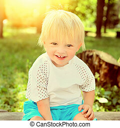 Toned Photo of the Cheerful Child on the Bench at the Summer Park