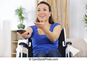 cheerful disabled woman watching television in living room