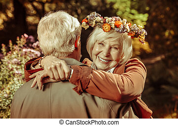 Cheerful elderly woman hugging her husband in a park.