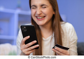 Cheerful female using mobile phone while doing online payment with bank card on purple background.