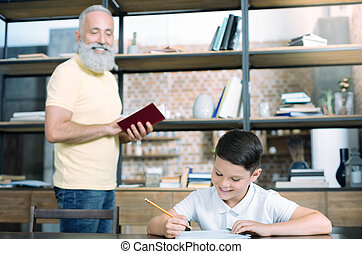 Cheerful grandfather looking at child working on home assignment