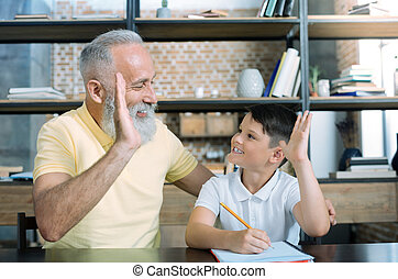 Cheerful grandson and grandfather high fiving at home