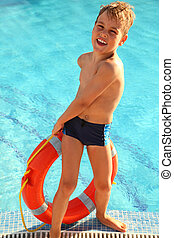 Cheerful little boy pulls out red buoy from the swimming-pool