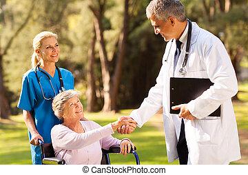 medical doctor handshaking with senior patient