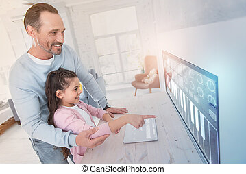 Cheerful parent smiling while helping his child to point to the screen