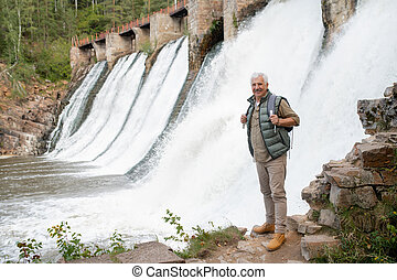 Cheerful retired male backpacker looking at you while standing by waterfalls