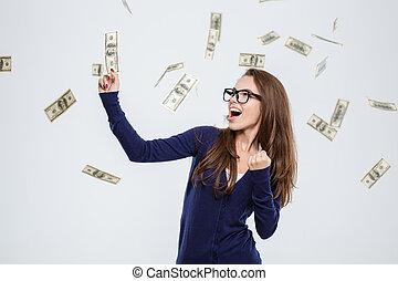 Cheerful woman standing under rain of money