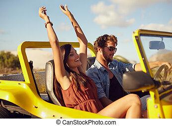 Cheerful young couple enjoying road trip