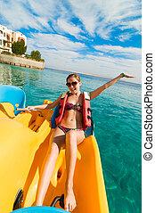 Cheerful young woman riding catamaran