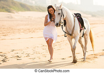 cheerful young woman walking with a horse on beach
