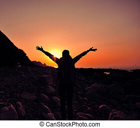 cheering hiking woman open arms on sunrise seaside